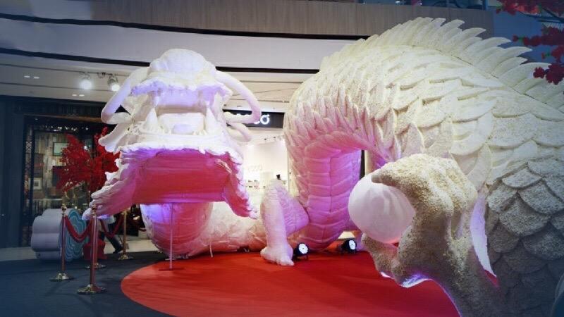 In het winkelcentrum CentralPlaza van Korat ligt een enorme draak tijdens het Chinees nieuwjaar te wachten op de os