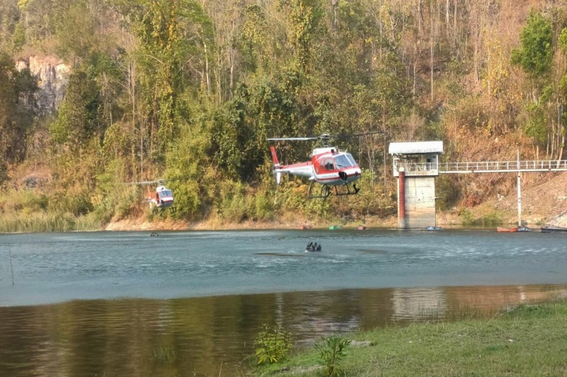 De bosbrand in het district Samoeng in Chiang Mai met behulp van helicopters bedwongen