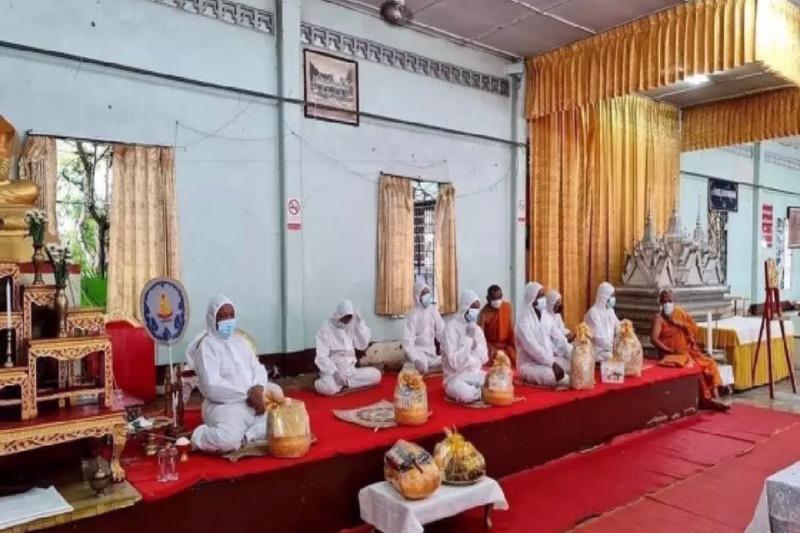 De monniken in de provincie Songkhla dragen PBM-pakken om begrafenisrituelen om uit te voeren