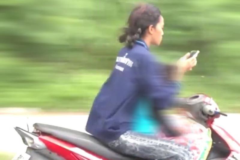 Tiener crasht met haar motor in geparkeerde auto terwijl ze op haar telefoon aan het koekeloeren was
